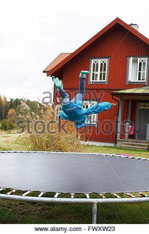 Sweden, Sodermanland, Jarna, Boy (6-7) jumping on trampoline - Stock Photo