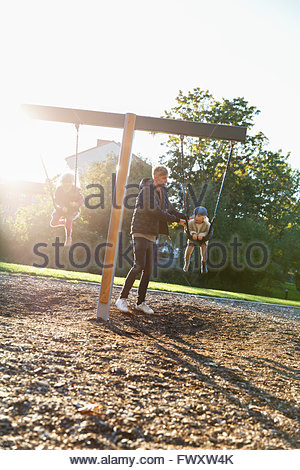 Sweden, Sodermanland, Arsta, Father with son (4-5) and daughter (2-3) swinging on playground at sunlight - Stock Photo