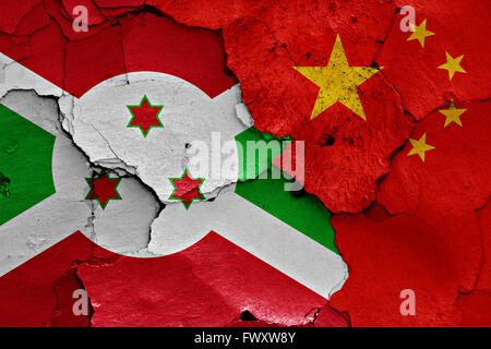 flags of Burundi and China painted on cracked wall - Stock Photo