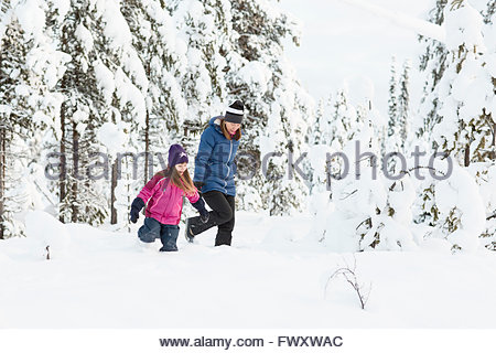 Sweden, Lapland, Gallivare, Girl (4-5) exploring forest with mother - Stock Photo