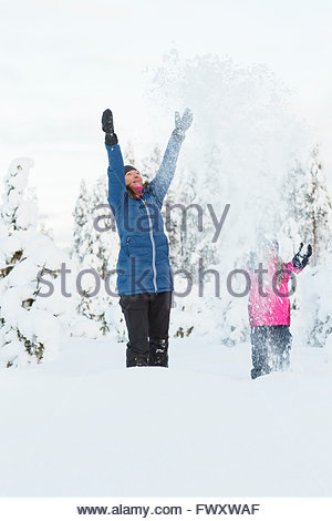 Sweden, Lapland, Gallivare, Girl (4-5) throwing snow with mother - Stock Photo