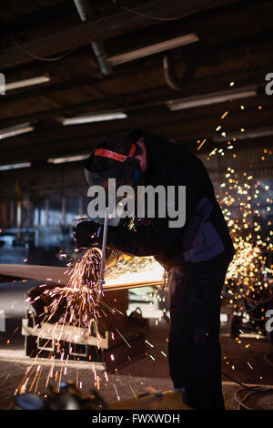 Sweden, Young man cutting metal in workshop - Stock Photo