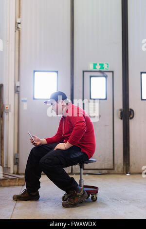 Sweden, Teenage boy (16-17) sitting and using phone - Stock Photo