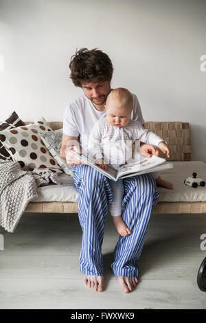 Sweden, Father reading to son (12-17 months) - Stock Photo