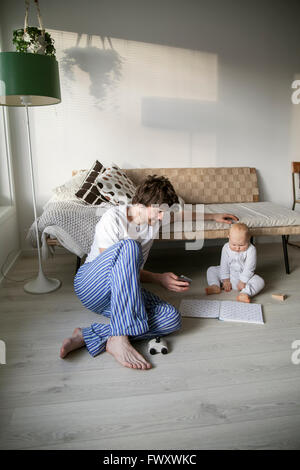 Sweden, Father and son (12-17 months) sitting on floor in living room - Stock Photo