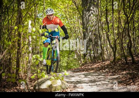Sweden, Blekinge, Solvesborg, Ryssberget, Mature man riding on mountain bike through forest - Stock Photo