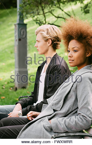 Sweden, Vastra Gotaland, Young couple sitting on bench in park - Stock Photo