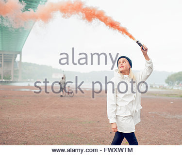 Sweden, Vastra Gotaland, Gothenburg, Young woman walking with distress flare - Stock Photo