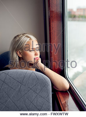 Sweden, Vastra Gotaland, Gothenburg, Young woman looking through window in train - Stock Photo