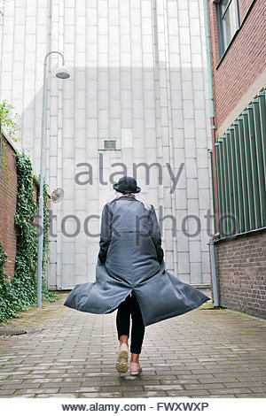 Sweden, Vastra Gotaland, Young woman wearing long overcoat walking away - Stock Photo