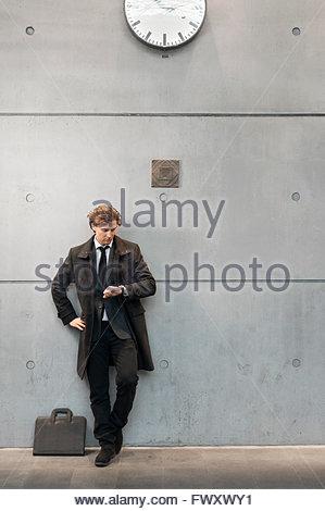 Sweden, Skane, Malmo, Businessman checking time on railroad station platform - Stock Photo
