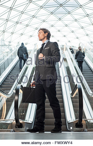 Sweden, Skane, Malmo, Businessman standing by escalator - Stock Photo