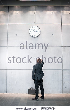 Sweden, Skane, Malmo, Businessman checking time at railroad station - Stock Photo