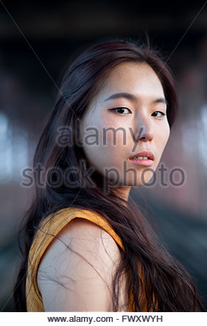 India, Uttar Pradesh, Varanasi, Portrait of young woman under bridge - Stock Photo