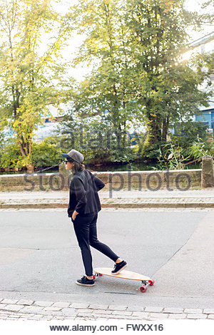 Sweden, Vastra Gotaland, Gothenburg, Young woman skateboarding - Stock Photo