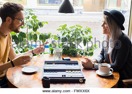 Sweden, Vastra Gotaland, Woman and man playing backgammon in cafe - Stock Photo