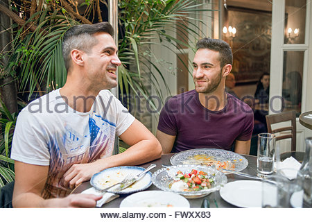 Israel, Tel Aviv, Smiling gay couple having dinner in restaurant - Stock Photo