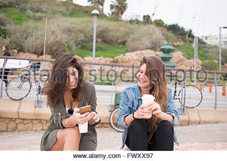 Israel, Tel Aviv, Women drinking coffee by promenade - Stock Photo
