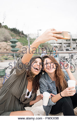 Israel, Tel Aviv, Two smiling women taking selfie - Stock Photo