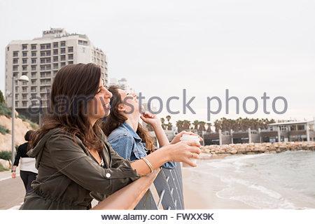 Israel, Tel Aviv, Two women standing by railing of promenade - Stock Photo