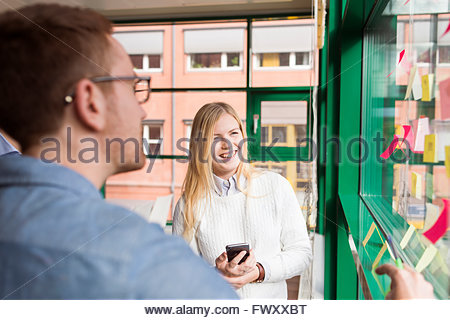 Sweden, Colleagues looking at adhesive notes in office - Stock Photo