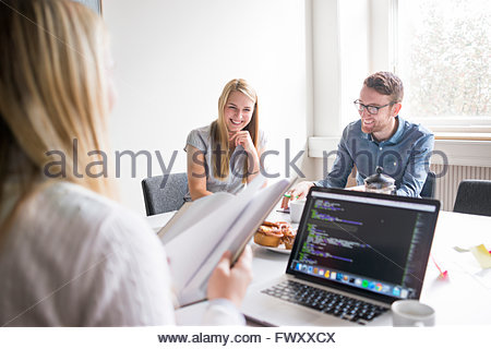 Sweden, Business people laughing in board room - Stock Photo