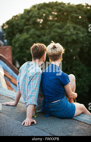 Germany, Berlin, Young couple sitting on rooftop with beer - Stock Photo