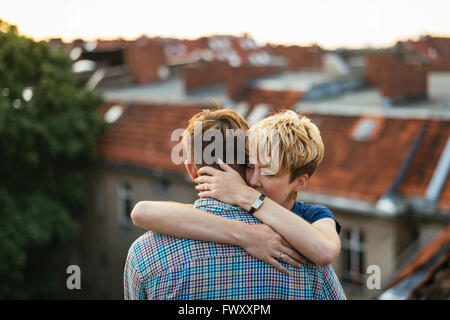 Germany, Berlin, Young couple hugging on rooftop at sunset - Stock Photo