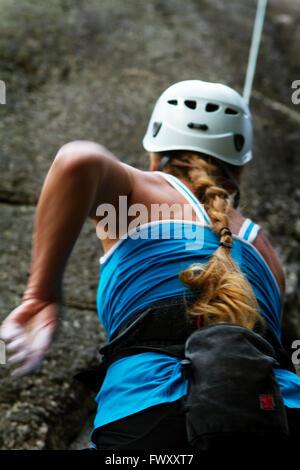 Sweden, Ostergotland, Vaderstad, Rear view of woman climbing rock - Stock Photo