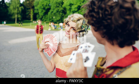 Sweden, Uppland, Hagaparken, Young circus performers holding playing cards in park - Stock Photo