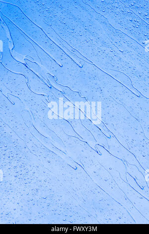 Water drops on window pane during a rainy day - Stock Photo