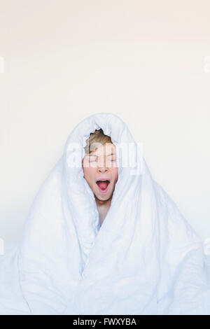 Finland, Helsinki, Portrait of yawning young man wrapped up in white blanket - Stock Photo