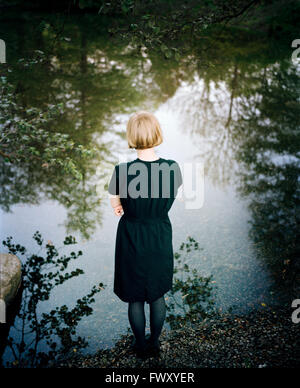 Finland, Varsinais-Suomi, Young woman standing at edge of lake - Stock Photo