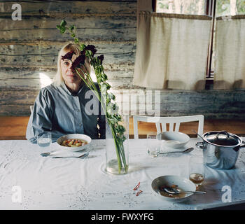 Finland, Mature woman sitting at table - Stock Photo