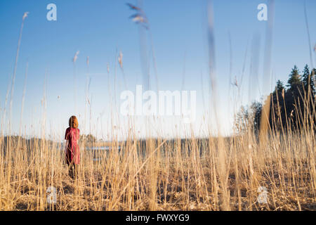 Finland, Varsinais-Suomi, Young woman standing in field in sunlight - Stock Photo