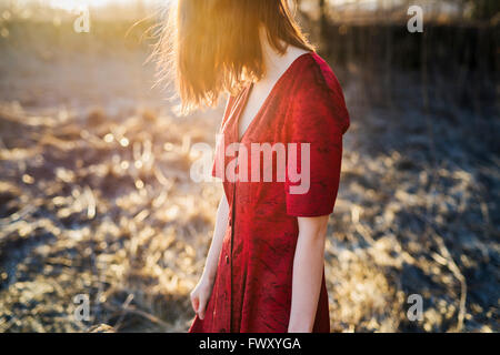 Finland, Varsinais-Suomi, Young red hair woman in red dress standing in sunlight - Stock Photo