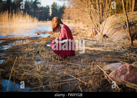 Finland, Varsinais-Suomi, Young woman crouching in wetlands - Stock Photo