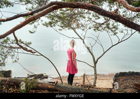 Finland, Varsinais-Suomi, Young woman looking at ocean - Stock Photo
