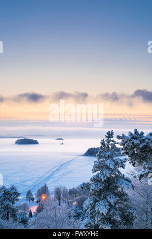 Finland, Pirkanmaa, Tampere, Landscape with frozen lake at dusk - Stock Photo