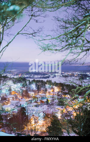 Finland, Pirkanmaa, Tampere, High angle view of illuminated city at dusk - Stock Photo