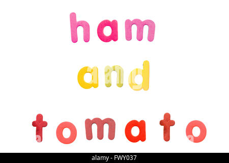 Ham and Tomato spelled with alphabet fridge magnets photographed against a white background. - Stock Photo