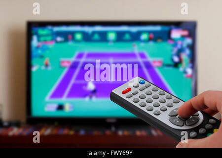 Watching a tennis match in the television, with a tv remote control in the hand - Stock Photo