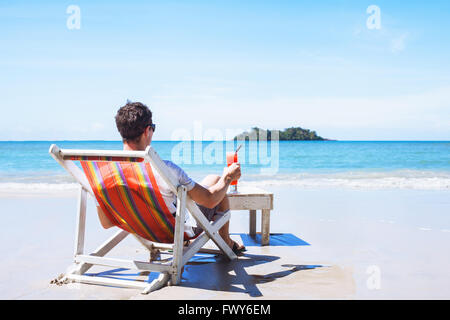 man relaxing on private beach on paradise island, luxurious holidays, tourist with cocktail sitting near the sea - Stock Photo