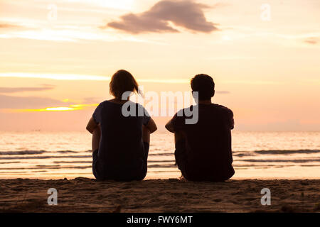 friends sitting together on the beach and watching sunset, friendship concept - Stock Photo