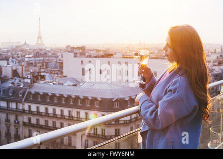 woman enjoying panoramic view of Paris and Eiffel tower at sunset, holding glass of wine or champagne in rooftop - Stock Photo