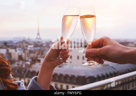 two glasses of champagne or wine, couple in Paris, romantic celebration of engagement or anniversary - Stock Photo