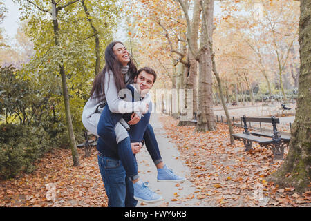 happy young couple having fun in autumn park, caucasian family, man and woman, piggyback - Stock Photo
