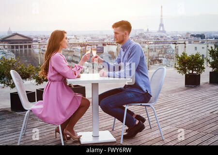 couple drinking champagne in luxury rooftop restaurant in Paris with panoramic view of Eiffel Tower - Stock Photo