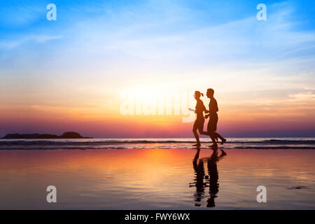 workout background, two people jogging on the beach at sunset, runners silhouettes, healthy lifestyle concept - Stock Photo
