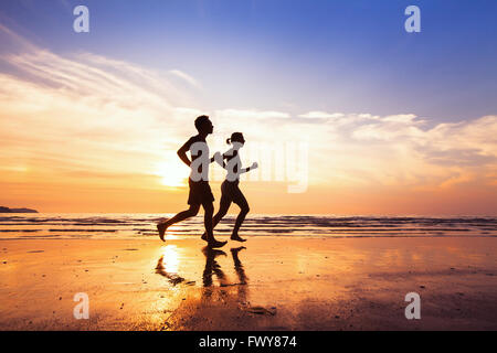 sport and healthy lifestyle, two people jogging at sunset on the beach - Stock Photo